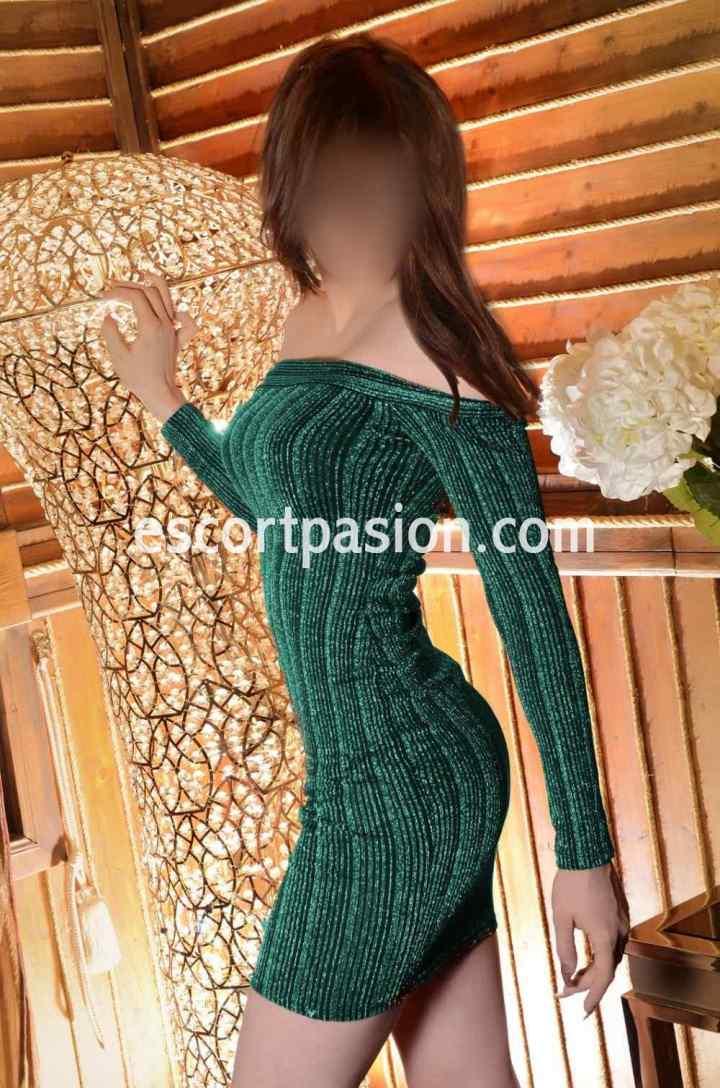 Puta en Marbella con vestido verde mirando hacia atrás